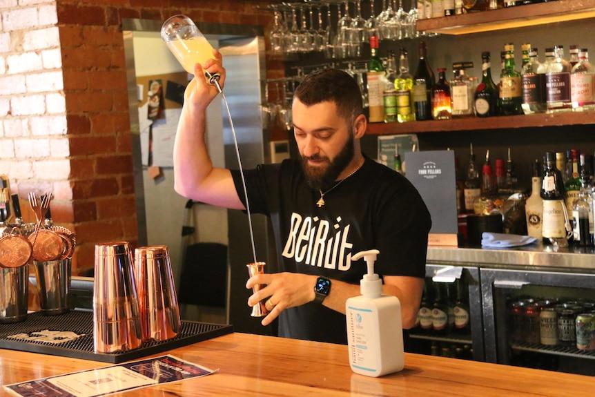 A man pours a shot at a bar