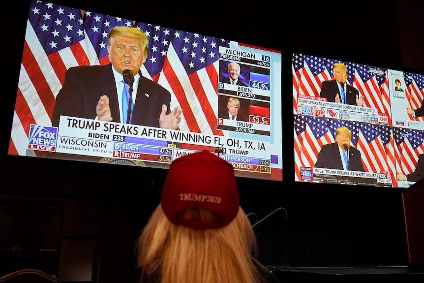 An image of a woman from behind watching US President Donald Trump on multiple TV screens.