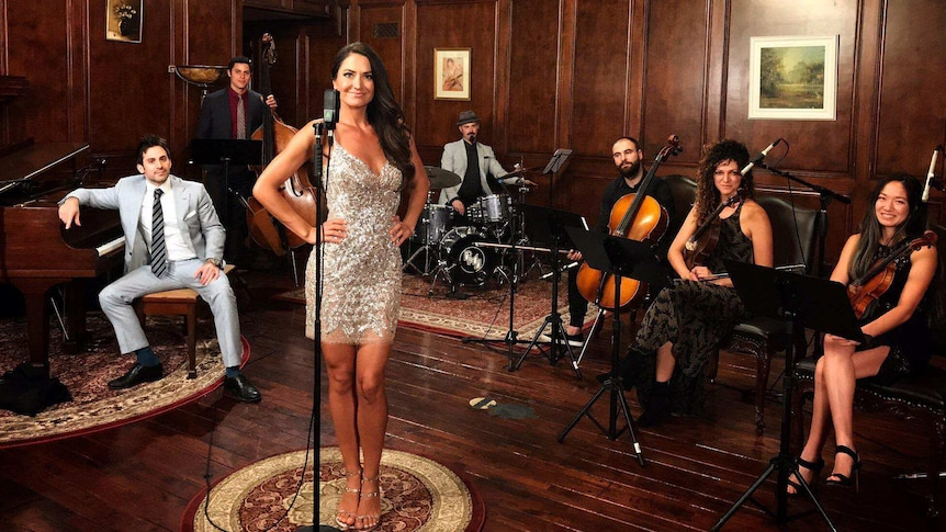 Postmodern Jukebox performers pose in a room with wooden floor and walls with instruments.