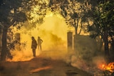 Two firefighters in protective gear fight a bushfire from a path with the area covered in smoke.