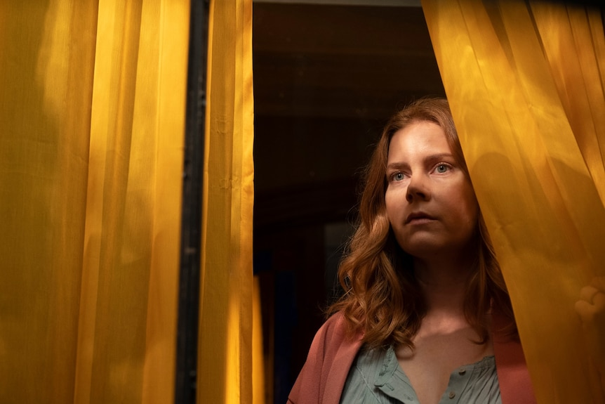 Film still of Amy Adams as Anna cast in shadow looking out the window through yellow curtains in The Woman in the Window