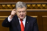 Petro Poroshenko raises a finger to point during a session in parliament