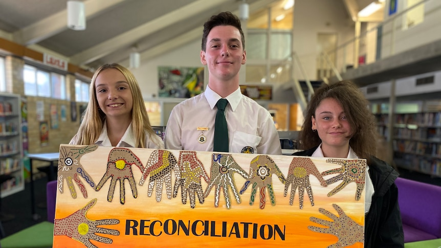 Two young women and a young man hold a painting which says reconciliation
