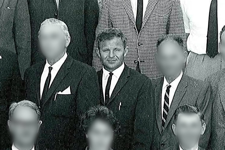 A black and white photo of a group of men with all but one of their faces blurred.