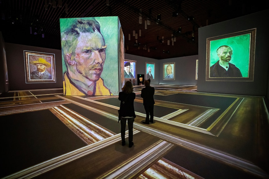 People stand in a gallery space displaying Van Gogh self portraits