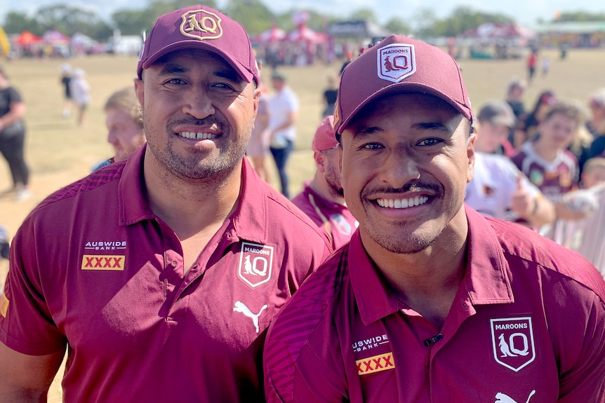 Two men wearing Queensland Maroons rugby league uniforms.