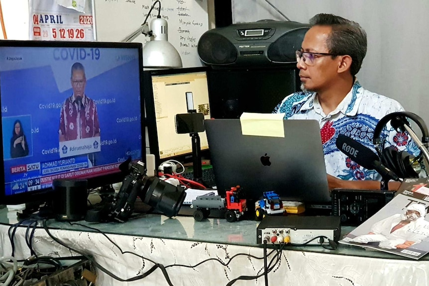 Wu sitting at desk surrounded by microphone, laptop and camera equipment looking at TV screen with man talking about Covid-19.