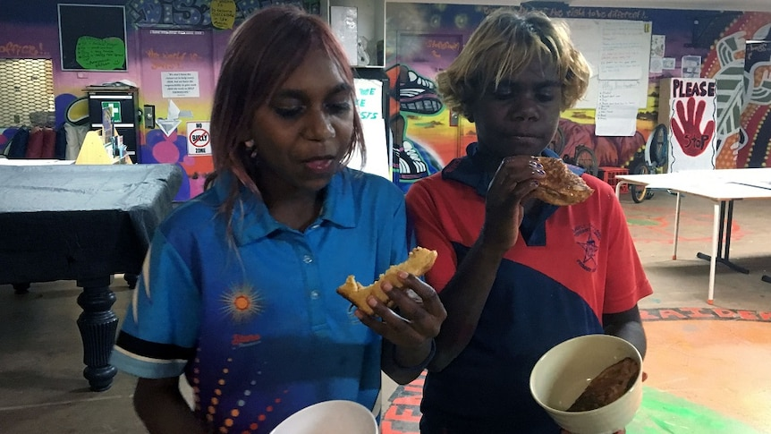 Two Indigenous children eat toast out of bowls at the youth centre