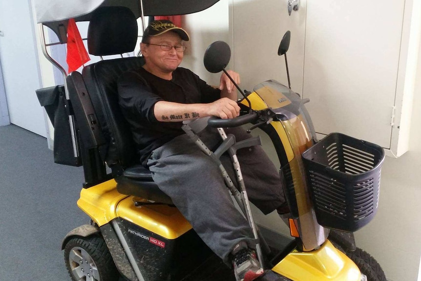 A man with glasses sits in a wheelchair with a an ACDC T-shirt on