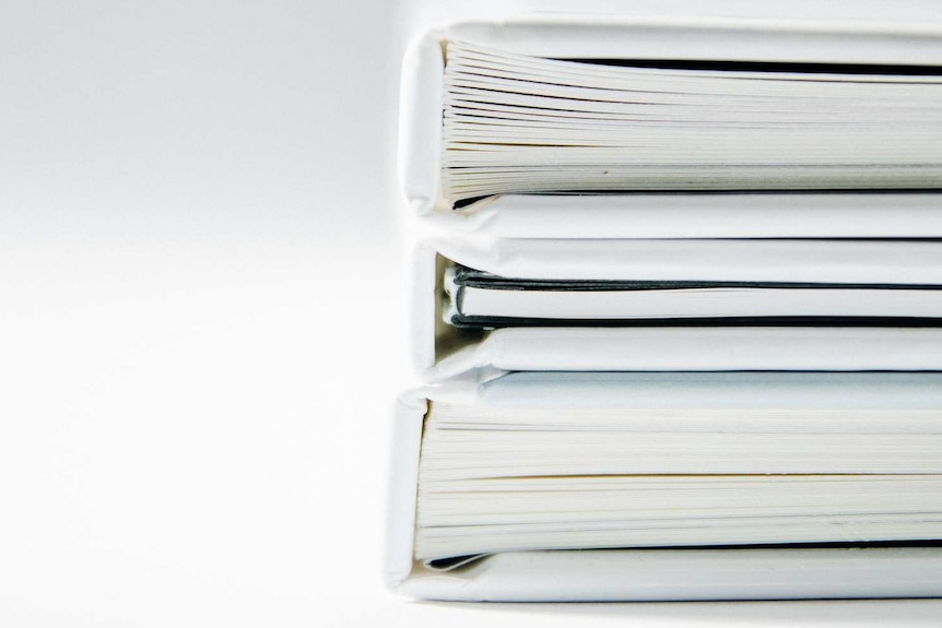Stacked binders of dicuments.