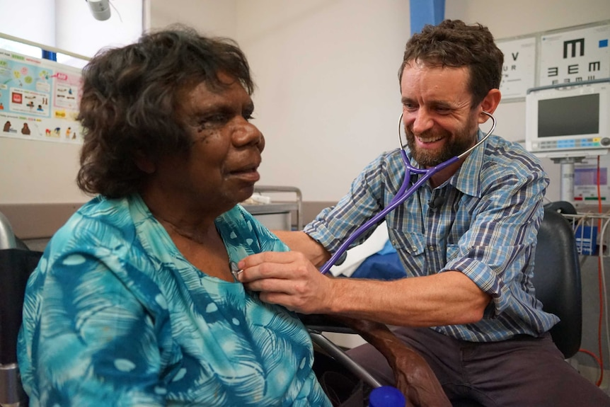 A doctor listens through his stethoscope to a seated Indigenous woman's heart in a examination room.