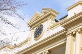 A close up of a clock on top of a building