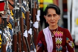 Aung San Suu Kyi walking alongside a row of soldiers holding guns