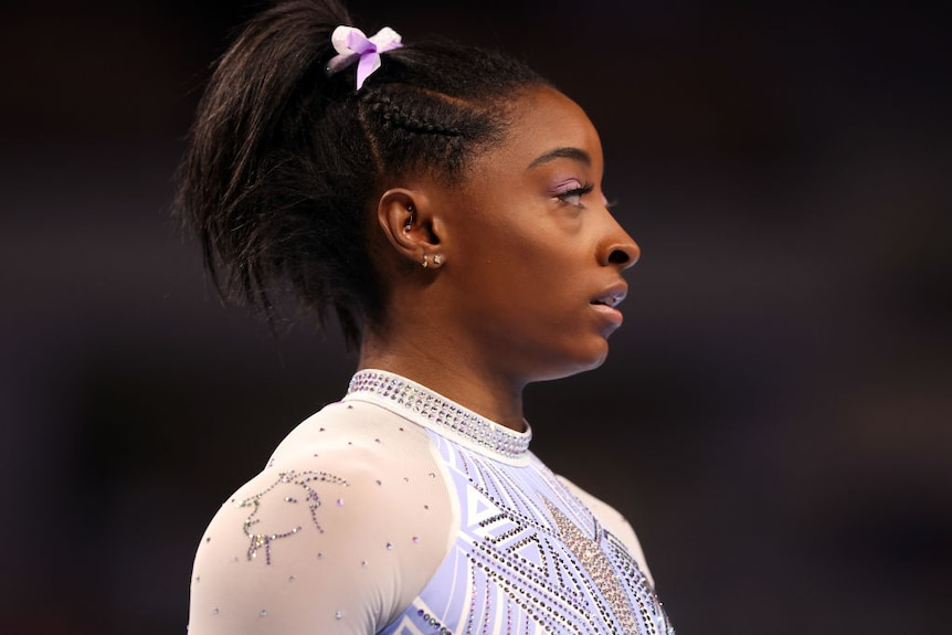 a head-and-shoulders image of gymnast simone biles with a bejewelled goat on the shoulder of her leotard