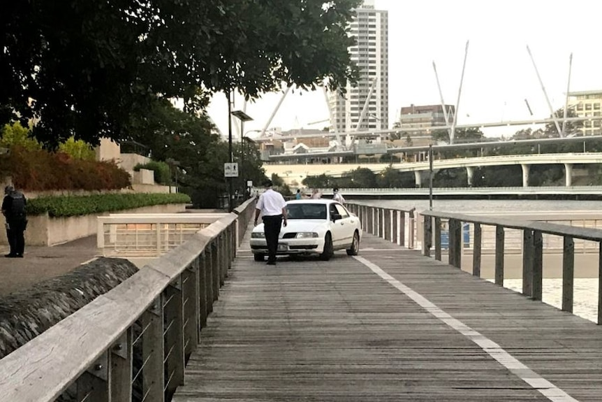 Security guard inspects a car which had been driven down a boardwalk along the Brisbane River.