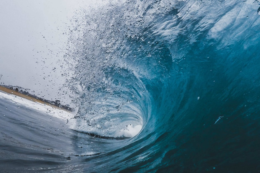 A shot from inside a barrel wave as it crashes near shore with the beach in the distance.