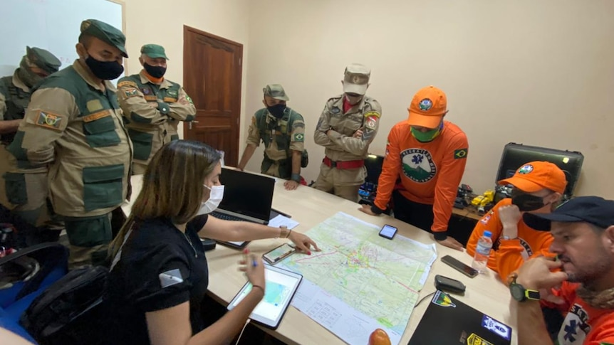 A dozen men in orange and green uniforms study a map on a conference table