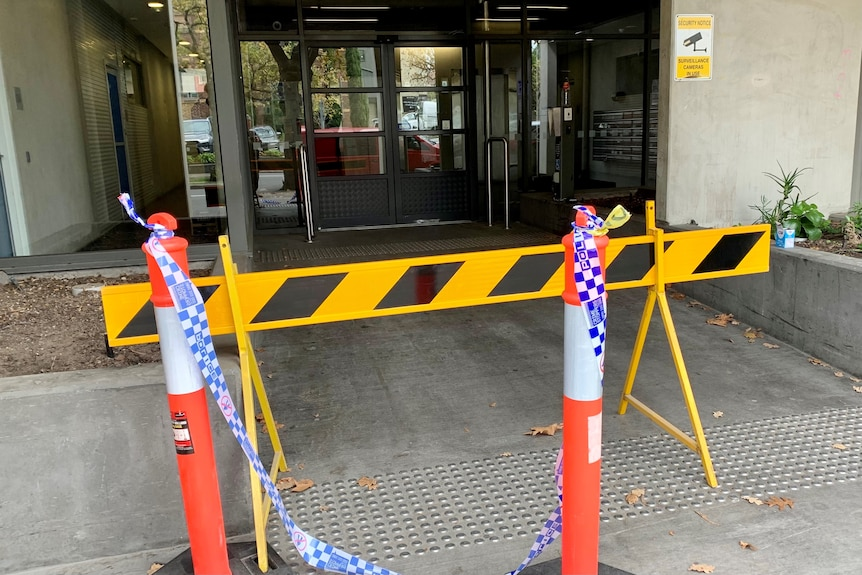 Police tape across the entrance of an apartment block.