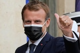 French President Emmanuel Macron gives the thumbs up while wearing a mask