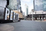 An empty Yagan Square in Perth with the large Yagan Square sign on the left and the CBD in the background.
