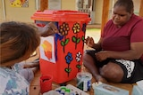 Two Aboriginal women sitting down outside painting a red bin