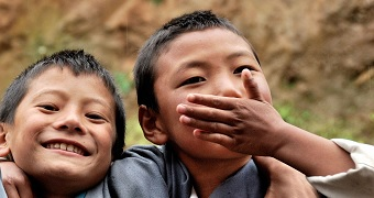 One boy, who is smiling, is standing next to another boy who has one hand over his mouth.