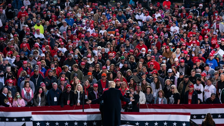 President Donald Trump speaks in front of a large crowd during a campaign rally