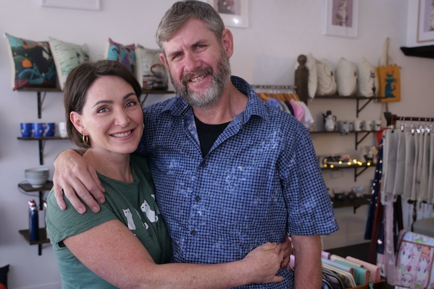 Tracey wrapped her arms around Richard, both smiling, surrounded by cat gifts.