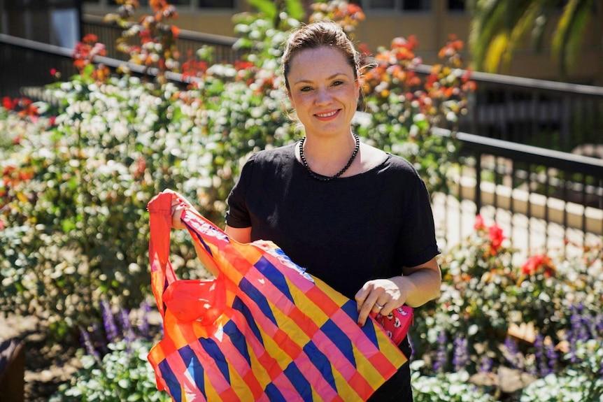 Sarah Quinton holding a colourful reusable shopping bag.