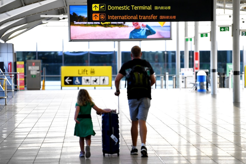 A man and his daughter walk with luggage at the domestic terminal in Brisbane airpor.
