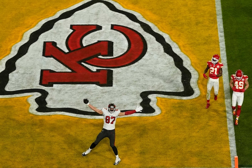 Rob Gronkowski puts his arms out to celebrate a Tampa Bay Buccaneers touchdown on the Kansas City Chiefs logo.