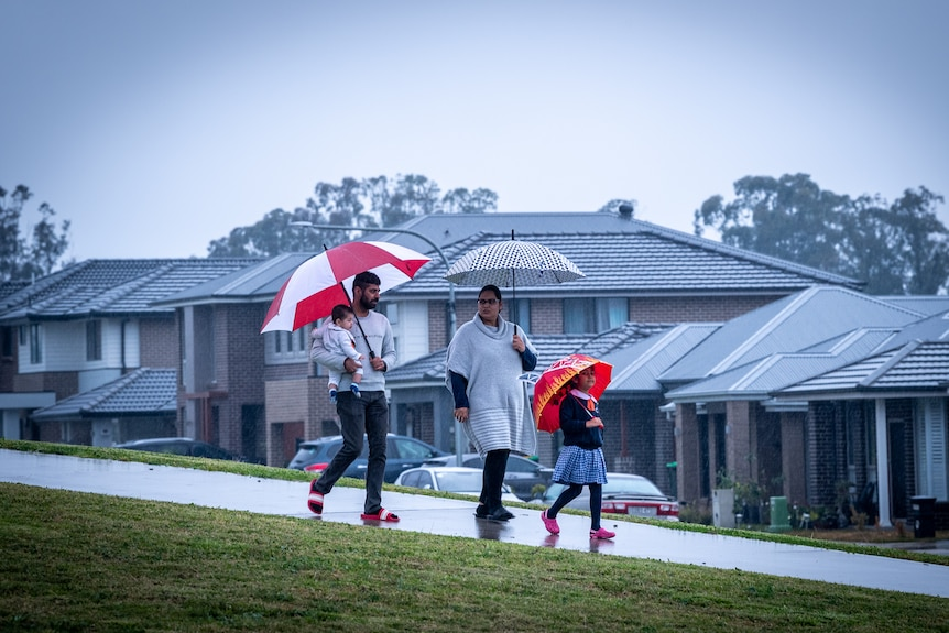 A young family walk down a footpath on a rainy day. Mum, Dad and little girl are all holding umbrellas