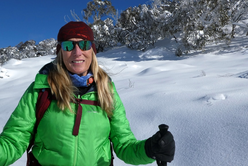 A woman wearing a green jacket and glasses stands in the snow.