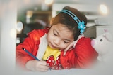 A young girl concentrates as she writes with a pencil