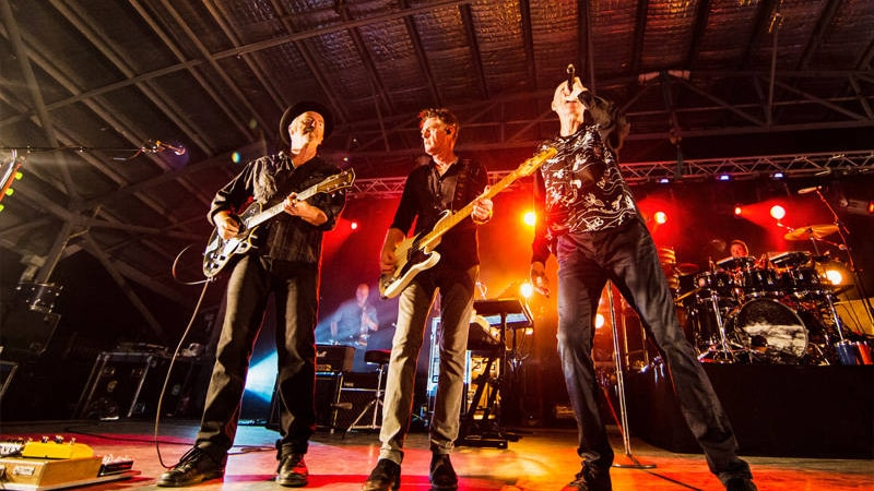 Three members of Midnight oil standing besides each other on stage at the Kuranda Amphitheatre