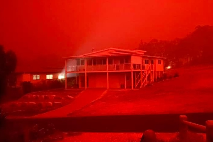 A vivid, red hue colours the entire view of a home in Mallacoota.
