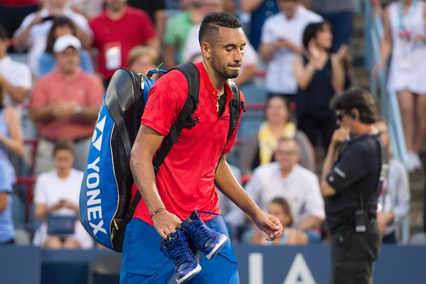 Nick Kyrgios walks off the court carrying his bag and shoes.
