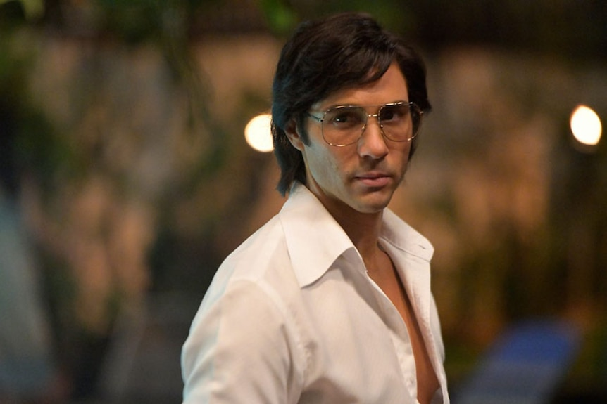Tahar Rahim in a 70s style white shirt and glasses.