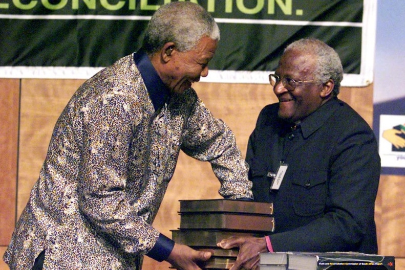 Nelson Mandela accepts stacked books of the Truth and Reconciliation Commission's report from Archbishop Desmond Tutu.