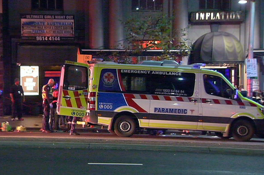 An ambulance Victoria parked outside of at Inflation nightclub, with its back doors open and police on scene.