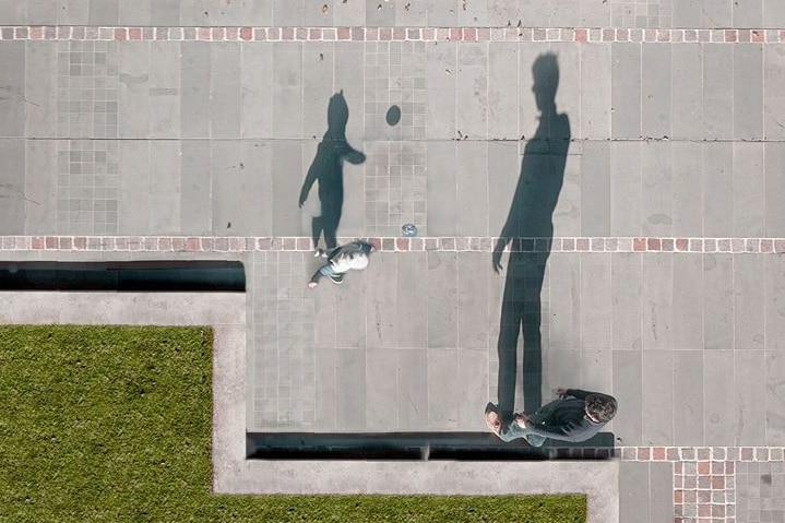 Silhouettes of a boy and his father kicking a ball.