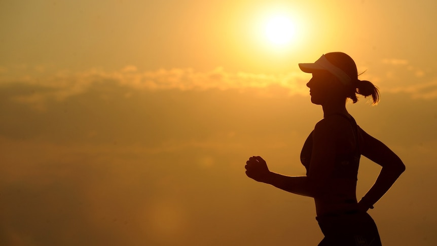 Silhouette of woman running with sunshine in the background