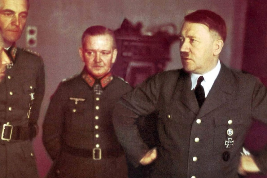 Three German generals in uniform standing next to Adolf Hitler who has his hands on his hips