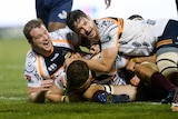 two players celebrate as a player in a headband plants the ball over the try line