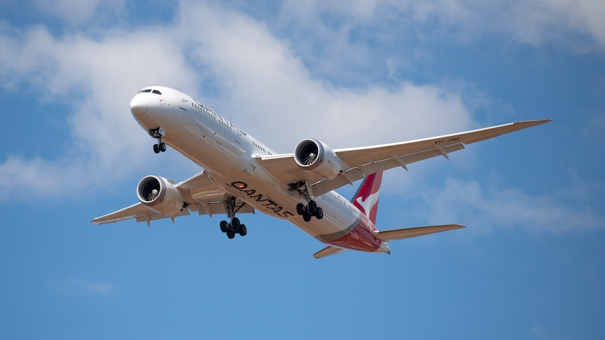 A photo of a Qantas plane flying in the sky.