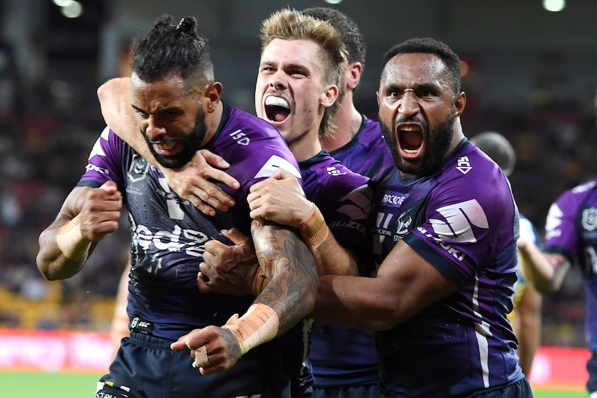 Three Melbourne Storm NRL players embrace as they celebrate a try scored against Parramatta.