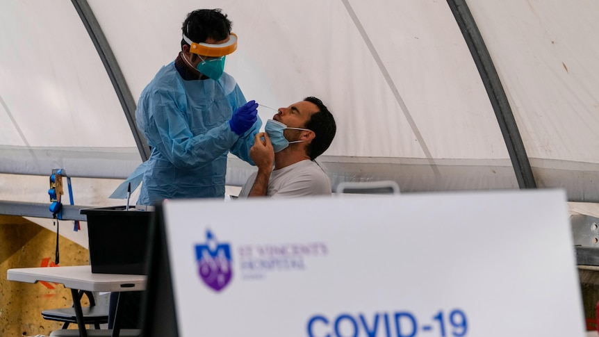 A healthcare worker takes a nasal swab from a man at St Vincents hospital in Sydney