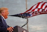Trump opens his mouth to speak at a podium and an America flag billows behind him, looking like it's coming out of his mouth