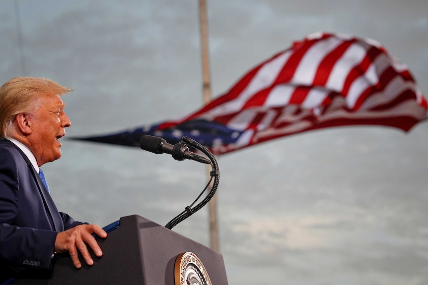 A man with orange hair speaks at a microphone while a US flag looks like it's floating out of his mouth.