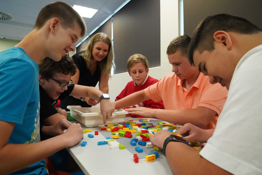 A group of five students and Melissa sit around a table and work with the braille bricks.
